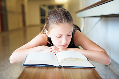 Young girl laying on bench reading a book; Toronto, Ontario, Canada - p442m1086641 by Vast Photography