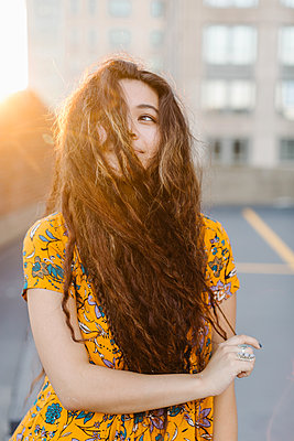 Portrait of young girl pulling long wavy hair across face in parking lot - p924m1180248 by Lena Mirisola
