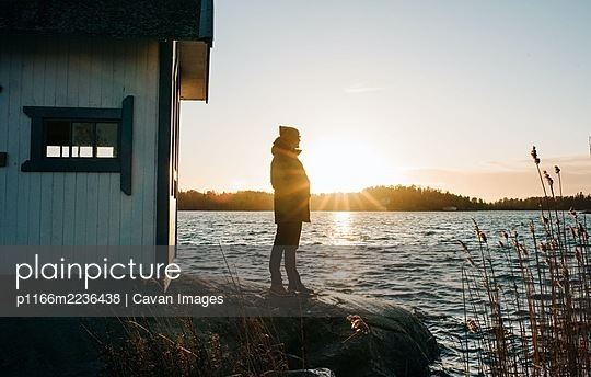 person stood on a rock next to a wooden hut in Sweden at sunset - p1166m2236438 by Cavan Images
