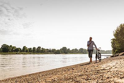 Mature man with bike using smartphone at Rhine riverbank - p300m2004762 von Uwe Umstätter