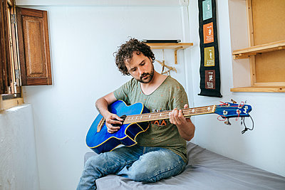 Spain, Man playing bass guitar in his room - p300m2012709 von Kiko Jimenez