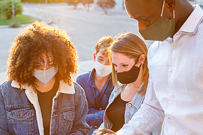 Male and female students discussing while wearing protective face mask in university campus - p300m2226541 by Ignacio Ferrándiz Roig