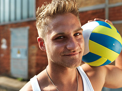 Germany, Duesseldorf, Young man with volley ball in industrial area, smiling, portrait - p300m752849f by Stefan Kranefeld