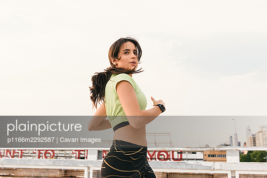 Jogger racing by from side profile in front on industrial buildings - p1166m2292587 by Cavan Images
