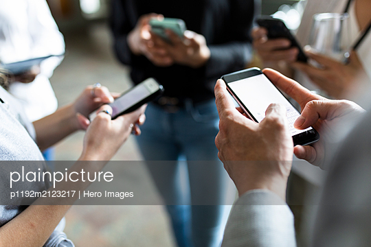 Business people using smart phones in circle - p1192m2123217 by Hero Images