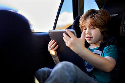 Cute boy using digital tablet while traveling in car during weekend - p1166m2201300 by Cavan Images