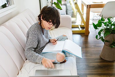 Child sitting with a sketch note book on sofa while checking on laptop - p1166m2224166 by Cavan Images