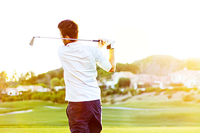 Rear view of man hitting golf ball against clear sky - p1166m969823f by Cavan Images