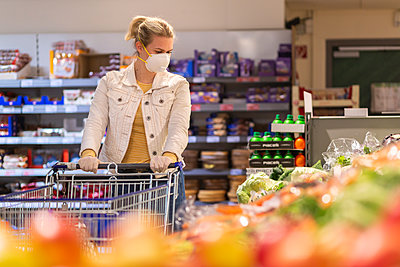 Teenage girl wearing protectice mask and gloves looking at vegetables at supermarket - p300m2225031 by Anke Scheibe