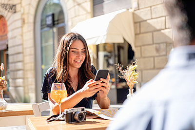 Smiling woman using mobile phone while sitting at sidewalk cafe - p300m2287521 by Emma Innocenti