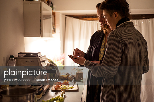 gay couple follow phone recipe in kitchen cooking healthy dinner - p1166m2258386 by Cavan Images