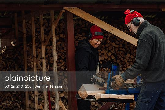 Senior couple using table saw - p312m2191256 by Jennifer Nilsson