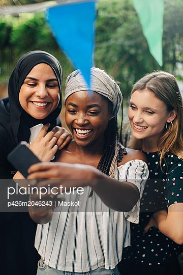 Happy multi-ethnic female friends taking selfie through smart phone in backyard - p426m2046243 by Maskot