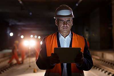 Serious male foreman using digital tablet at dark construction site - p1023m1448856 by Agnieszka Olek