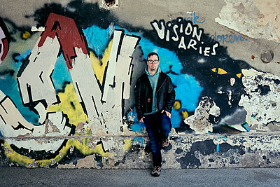Man with Down's syndrome leaning at graffiti wall - p1164m2175920 by Uwe Schinkel