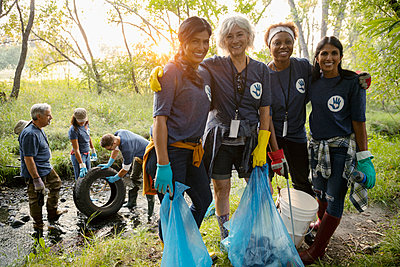 Portrait smiling women volunteering, cleaning up garbage in park - p1192m2024627 by Hero Images