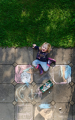 Smiling little girl drawing with chalk outdoors, top view - p300m1587311 by Hans Lippert