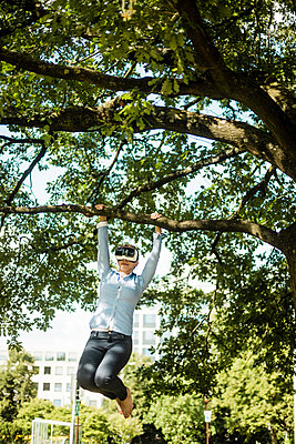 Woman in urban park hanging at branch of a tree wearing VR glasses - p300m2059242 by Robijn Page