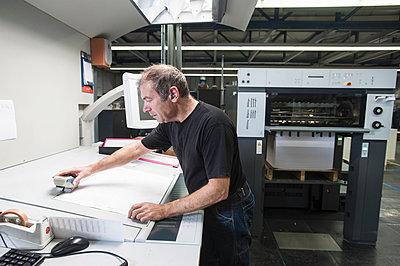 Worker preparing digital printing equipment in print workshop - p429m884712f by Arno Masse