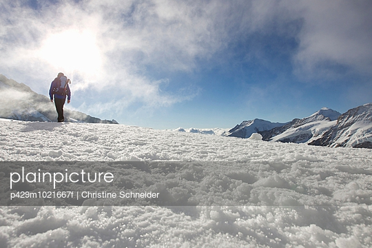 Low angle view of male hiker in snow covered landscape, Jungfrauchjoch, Grindelwald, Switzerland - p429m1021667f by Christine Schneider
