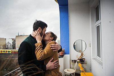 Junges Paar steht auf einem Balkon und knutscht  - p1301m1424726 von Delia Baum