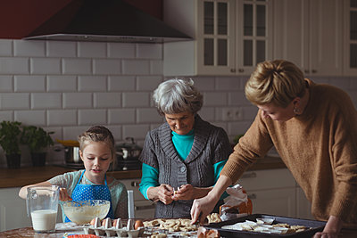 Multi-generation family preparing cupcake in kitchen at home - p1315m1566665 by Wavebreak