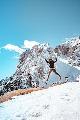 Young woman jumping at a mountain range in Kranjska Gora on a beautiful day - p1455m2077142 by Ingmar Wein