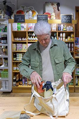 Barcelona, Spain. Senior man buying food in local organic store / Senior man with small business shop. Local, shot, small business, km0, organic, slow food, senior, shop, urban garden, city, grow food, vegetables - p300m2179958 von VITTA GALLERY