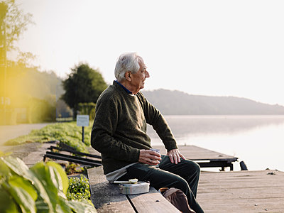 Senior man looking at view while sitting on bench - p300m2251642 by Gustafsson