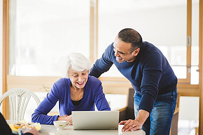Cheerful mature man standing by mother looking at laptop on table in nursing home - p426m2018587 by Maskot