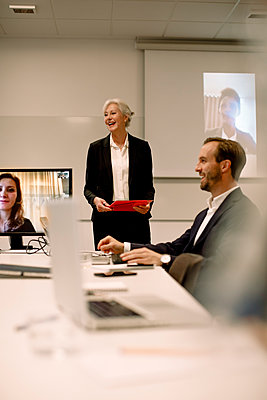 Smiling mature professional discussing with colleagues in video conference at board room - p426m2187220 by Maskot