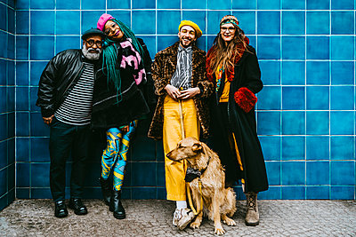 Full length of smiling men and women with dog against blue wall - p426m2279717 by Maskot