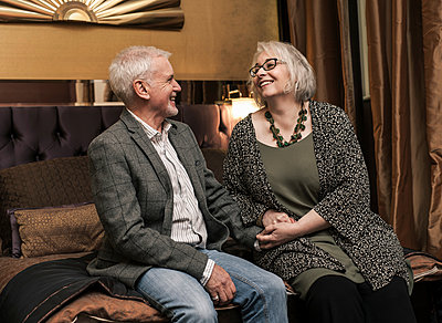 Senior couple smiling and chatting on bed - p429m1206983 by Colin Hawkins