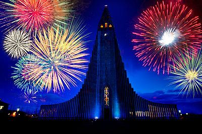 Fireworks exploding over monument in night sky, Reykjavik, Hofudborgarsvaedi, Iceland - p555m1415710 by Pete Saloutos