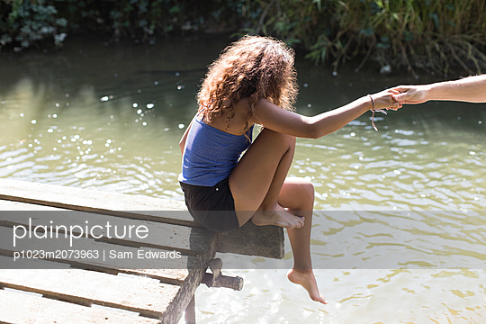 Girl sitting at the edge of sunny riverside dock - p1023m2073963 by Sam Edwards
