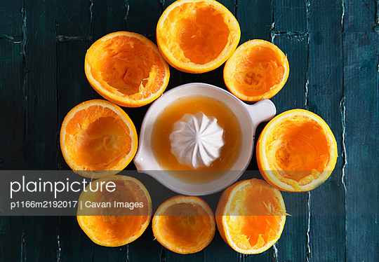 still life on a green wooden base of an orange squeezer with orange ju - p1166m2192017 by Cavan Images