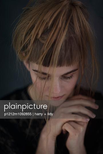 Junge Frau mit Hand am Kinn - p1212m1092855 von harry + lidy