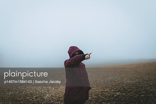 Junge Frau zeigt in eine Richtung im mystischen Nebel - p1497m1584143 von Sascha Jacoby