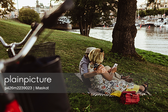 Rear view of senior couple using smart phone at lakeshore - p426m2239023 by Maskot