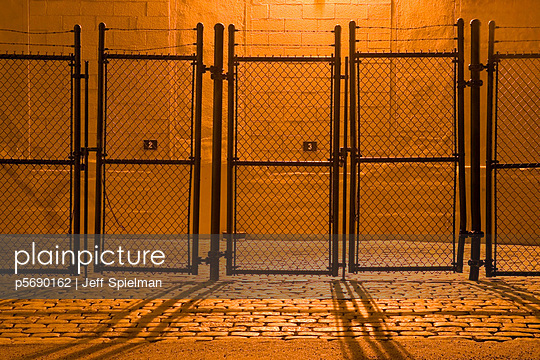 Fence at Night on Cobblestone Street - p5690162 by Jeff Spielman