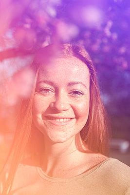 Glückliche Frau unter Kirschblütenzweig - p045m2082429 von Jasmin Sander