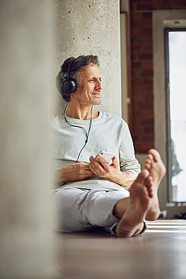 Senior man with headphones listening music in a loft flat - p300m2202793 by Maya Claussen