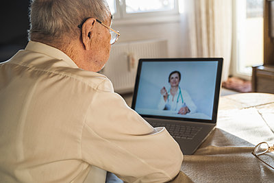 Senior man taking advice from female doctor on video through laptop in living room - p300m2243569 by Uwe Umstätter