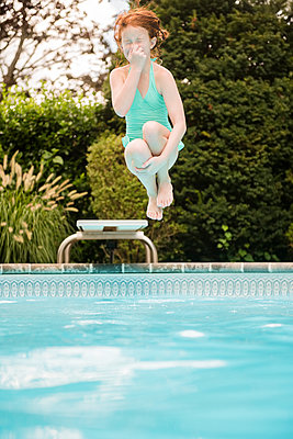 Caucasian girl holding nose jumping off diving board into swimming pool - p555m1303490 by JGI/Jamie Grill