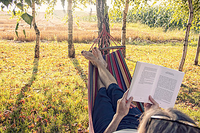 Woman in hammock reading a book - p879m2257739 by nico