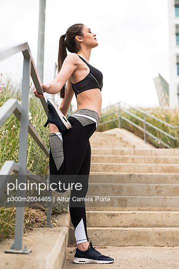 Sportive woman stretching leg - p300m2004465 von Aitor Carrera Porté