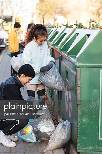 Young male and female environmentalists throwing recycling waste in garbage can - p426m2213248 by Maskot
