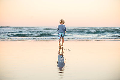 Little boy running towards waves at beach with reflection - p1166m2130492 by Cavan Images