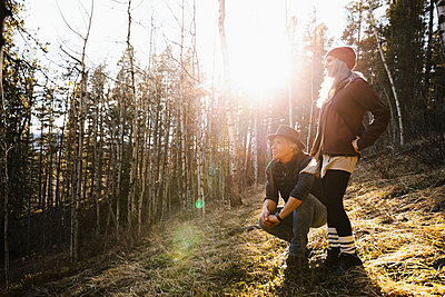 Serene couple hiking in sunny woods - p1192m2094271 by Hero Images