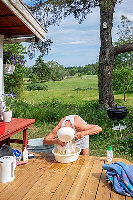 Frau wäscht ihre Haar in einer Schüssel im Garten - p1418m2099633 von Jan Håkan Dahlström